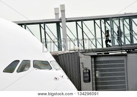 Unrecognizable people boarding into a big airplane