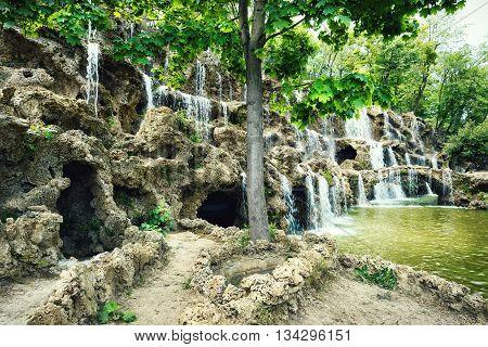 Waterfall in the sandy rocks under green trees