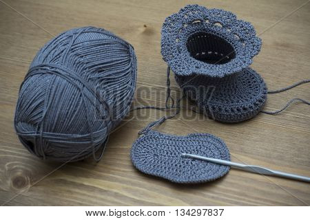 Knitted baby booties on a wooden background
