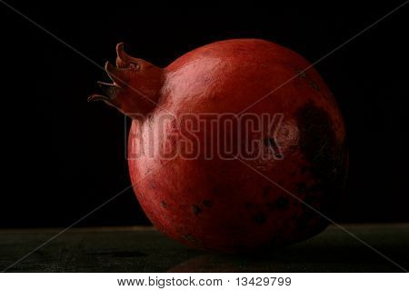 Red ripe pomegranate on a black background