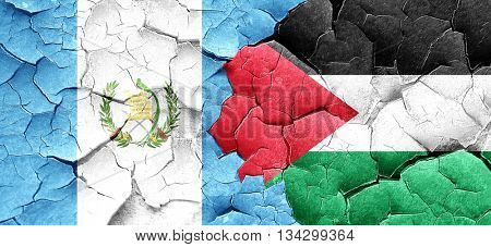 guatemala flag with Palestine flag on a grunge cracked wall