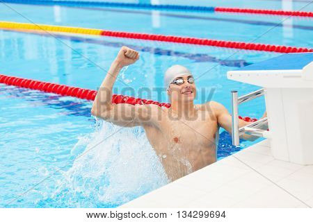 Young male swimmer celebrating victory in the swimming pool.