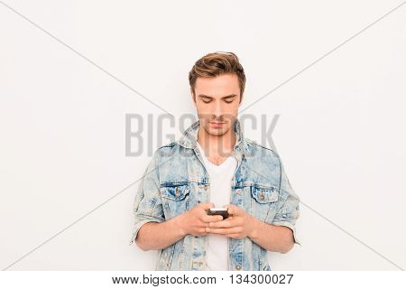 Handsome Young Guy In Jeans Jacket Typing Sms