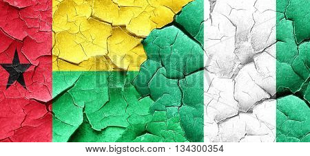 Guinea bissau flag with Nigeria flag on a grunge cracked wall