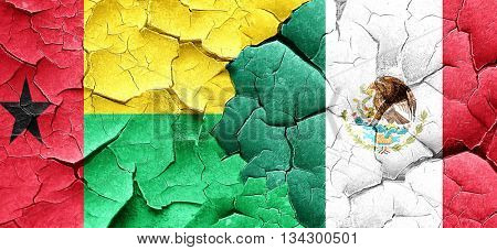 Guinea bissau flag with Mexico flag on a grunge cracked wall