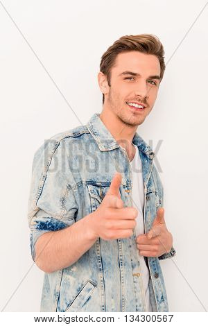 Handsome Young Cheerful Man In Jeans Jacket Pointing On Camera