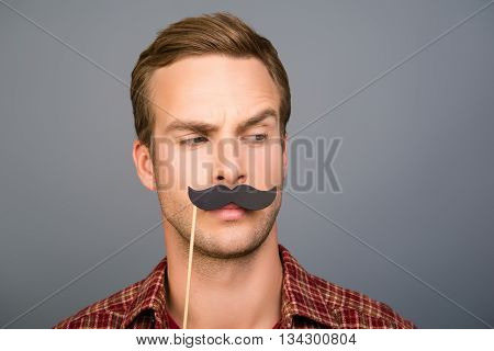 Portrait Of Pretty Young Man With Paper Mustache On Gray Background