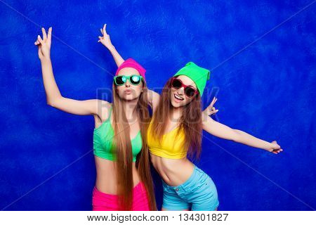Stylish Hipster Women In Color Clothes And Spectacles Gesturing With Two Fingers