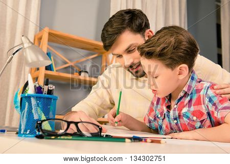 Happy Family. Father And Son Doing Homework Together