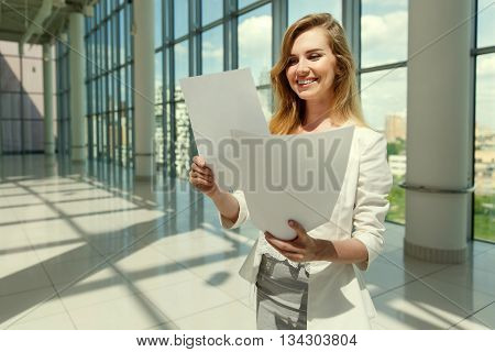 Businesswoman hold some documents against a big window. Image with split toned techniques