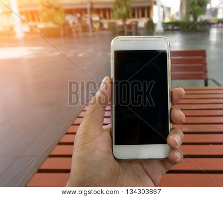 Man's Hand Shows Mobile Smartphone In Vertical Position, Blurred Background