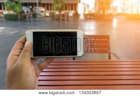 Man's Hand Shows Mobile Smartphone In Horizontal Position, Blurred Background