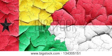 Guinea bissau flag with Indonesia flag on a grunge cracked wall