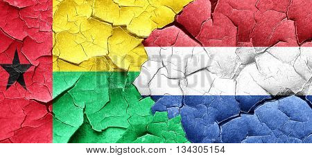 Guinea bissau flag with Netherlands flag on a grunge cracked wal