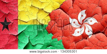 Guinea bissau flag with Hong Kong flag on a grunge cracked wall