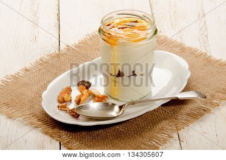 kefir in a glass with sweet honey nuts and fruit and spoon on oval plate