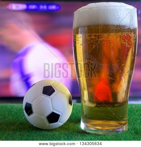 Glass of beer, soccer ball and tv , football match in background