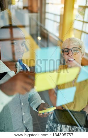 Team of young casual business people collaborating on an creative planning project using a blue and yellow sticky notes in a bright modern office space. Serie with light flares and glass reflections