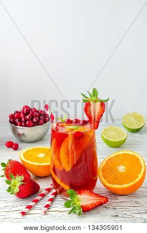 Sangria with oranges cranberries lime and strawberries in glasses white background. Refreshing summer drink juicy fruits and berries homemade lemonade