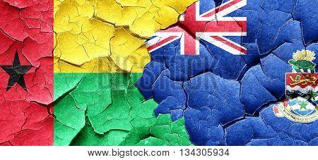Guinea bissau flag with Cayman islands flag on a grunge cracked