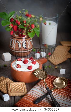 Strawberry with cream in a ceramic Cup, cookies and milk in glass on old wooden surface. Bouquet with strawberries in a ceramic vase and antique spoons on a napkin. The rustic style.
