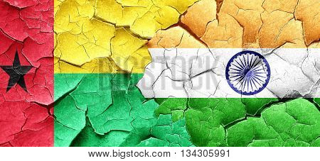 Guinea bissau flag with India flag on a grunge cracked wall