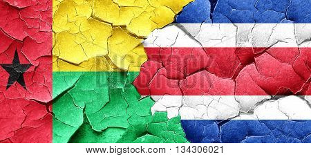 Guinea bissau flag with Costa Rica flag on a grunge cracked wall