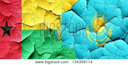 Guinea bissau flag with Kazakhstan flag on a grunge cracked wall