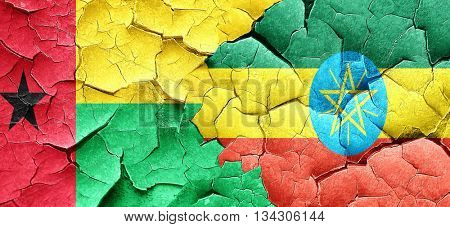 Guinea bissau flag with Ethiopia flag on a grunge cracked wall