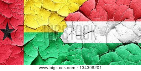 Guinea bissau flag with Hungary flag on a grunge cracked wall