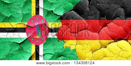 Dominica flag with Germany flag on a grunge cracked wall