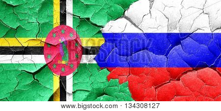 Dominica flag with Russia flag on a grunge cracked wall