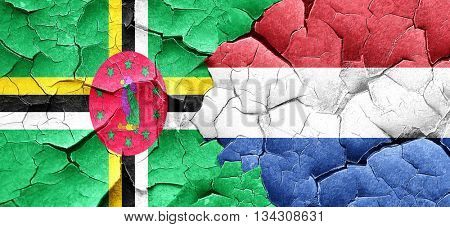 Dominica flag with Netherlands flag on a grunge cracked wall