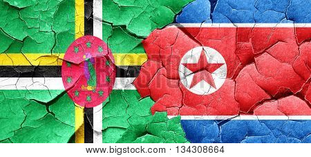 Dominica flag with North Korea flag on a grunge cracked wall