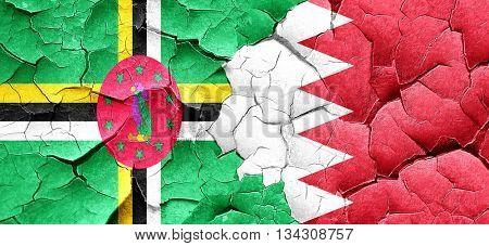 Dominica flag with Bahrain flag on a grunge cracked wall