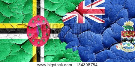 Dominica flag with Cayman islands flag on a grunge cracked wall