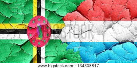 Dominica flag with Luxembourg flag on a grunge cracked wall