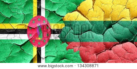 Dominica flag with Lithuania flag on a grunge cracked wall