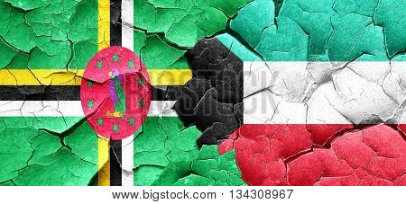 Dominica flag with Kuwait flag on a grunge cracked wall