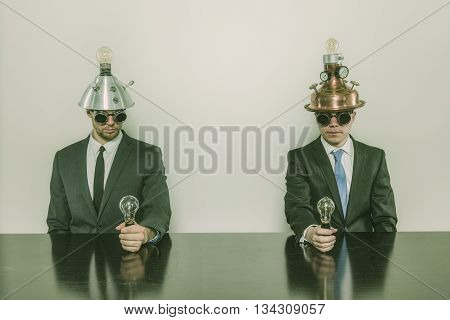 Two vintage businessman sitting at office desk with lamps