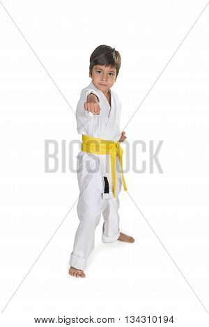 the boy stands in white kimono of the karateka with a yellow belt