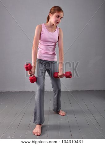 Teenage sportive girl is doing exercises to develop muscles on grey background. Sport healthy lifestyle concept. Sporty childhood. Teenager child exercising with wieghts.