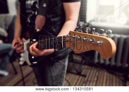 Bass guitar in playing musician hands close-up. Focus on bass guitar neck in player hands. Unrecoginzable bass guitar player performing at music studio, blurred background