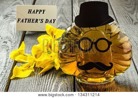 Fathers Day composition. Bottle with homemade fun applique in the shape of the face iris flowers and card with the words Happy Fathers Day. Selective focus