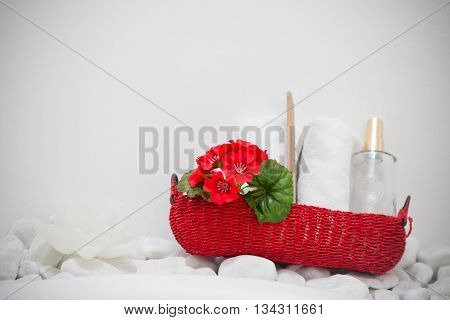 Red basket with decorative flowers and beauty products laid on the wall with white stones. Spa enviroment