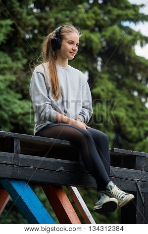 Cheerful athletic woman sitting resting after exercise in the park on the bench with phone and headphones.