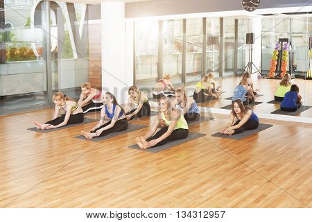 Group of young women in yoga class. Group of people making exercises. Girls do yoga stretching exercise, head to knee. Healthy lifestyle, sport, gymnastics, yoga studio. Fitness club, yoga training