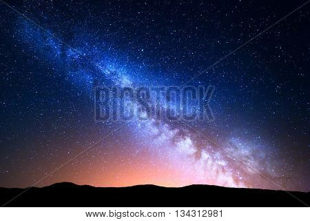 Night landscape with colorful Milky Way and yellow light at mountains. Starry sky with hills at summer. Beautiful Universe. Space background