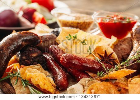 Closeup of beer snacks set. Assorted chips and sausages with red and yellow sauces. Colorful tasty beer snacks set