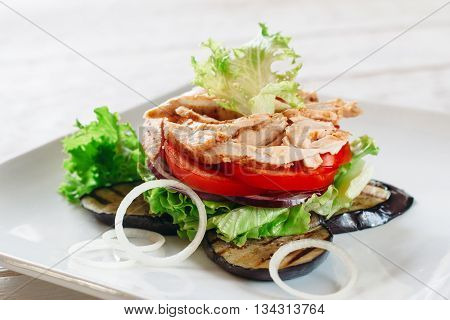 Layered salad with chicken, tomato and grilled eggplant on white. White square plate with portion of layered salad with fried chicken strips, tomato, lettuce, onion and grilled eggplant.
